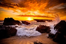 Sunset with waves crashing over rocks